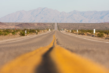 Classic horizontal panorama view of an endless straight road running through the barren scenery of the American Southwest on a beautiful day