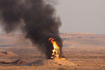 Fire and black smoke of burning oil during a fire power demonstartion of the Israeli Defence Forces in the Negev Desert