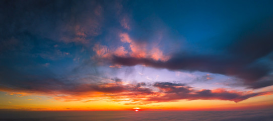 Panoramic aerial view of flying between the cloud at sunset