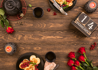 Valentine's day background with green tea, black teapot, candles, roses and wooden calendar. Valentines day concept. Top view. Copy space.