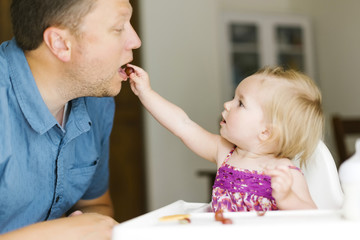 Baby girl (12-17 months) feeding her father