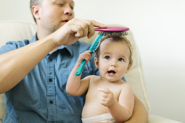 Father and baby girl (12-17 months) brushing hair after bath