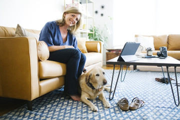 Woman stroking Labrador Retriever in living room