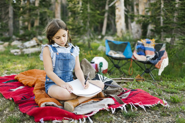 Girl (8-9) sitting on blanket in forest
