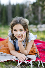 Portrait of girl (8-9) lying on blanket in forest