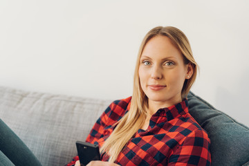 Pensive serious young woman on a sofa