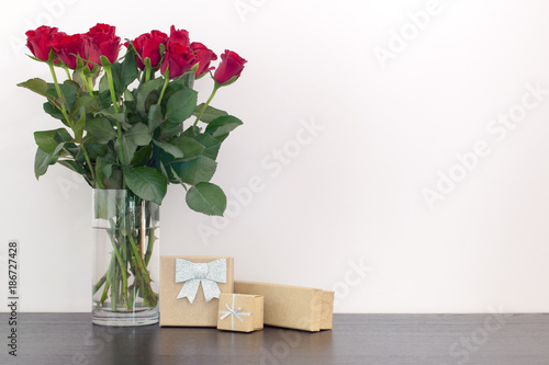 Beautiful Red Roses In A Vase And Gift Glitter Boxes On A Wooden