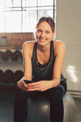 Smiling active young woman in a gym