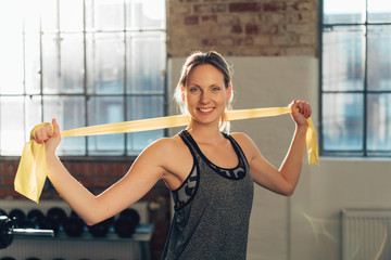 Fit healthy young woman working out with ribbons