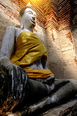Ancient Buddha and old brick wall on ancient monuments that are over 200 years old. Wat Nakhon Luang Tample,Prasat Nakhon Luang public domain or treasure of Buddhism in  Ayutthaya, Thailand