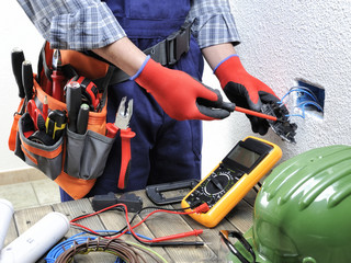 Young electrician technician works in compliance with safety standards in a residential electrical system.