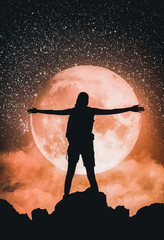 Woman silhouetted against a red super moon