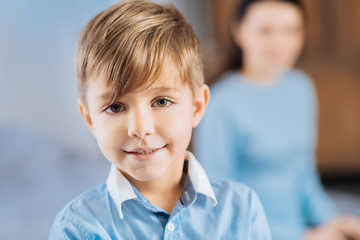 Adorable kid. The focus is on the face of a charming fair-haired little boy in a blue shirt smiling at the camera while his mother sitting behind him in the background