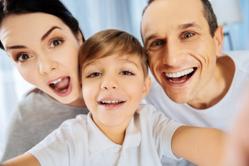 Perfect mood. The close up of a happy young family taking a selfie together, smiling at the camera and making funny faces
