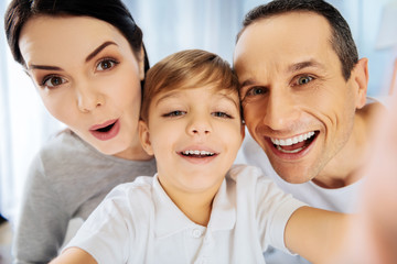 Upbeat mood. Adorable little boy taking a close-up selfie with his parents and all of them posing for the camera, smiling and making funny faces