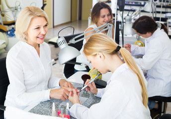 Female clients doing nails in nail salon in afternoon