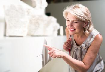 Mature woman standing in art museum near the antique sculpture