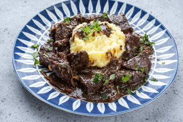 Fresh veal liver ragout in red wine sauce with mashed potatoes as close-up on a plate