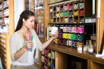 young woman picking candles in craft shop.