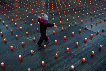 "A girl runs between candles during the ""One Million Stars"" event by Swiss humanitarian organisation Caritas as a sign of solidarity and cohesion with the infirm and the poor, in front of the Swiss Federal Palace (Bundeshaus) in Bern"
