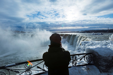 A vistor takes pictures of ice covered Niagara Falls in Niagara