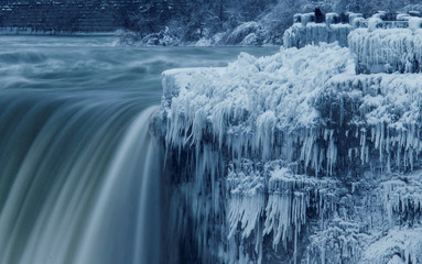 A lone visitor takes a picture near the brink of the ice covered Horseshoe Falls in Niagara Falls