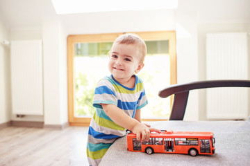 Smiling little italian kid with toy red bus in his hand