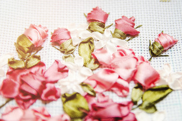 Beautiful flowers embroidered ribbon. Needlework, handicraft. Close-up, selective focus.