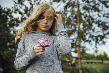 Low angle view of girl holding flower while standing on field