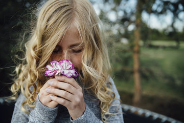 Close-up of girl smelling flower