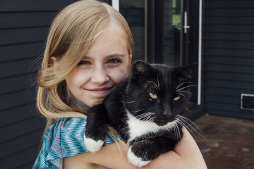 Close-up portrait of girl with cat standing against house