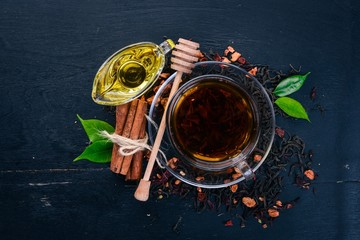 Tea in a cup of cinnamon and honey on a wooden background. Hot drink Top view. Copy space.
