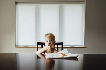 Portrait of shirtless boy eating bread while sitting by table at home
