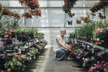 Portrait of mature woman crouching by plants at greenhouse