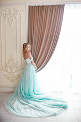 Luxury fashion pregnant blond woman in a wedding dress. Wedding pregnant woman. Girl is waiting the birth of a child. Elegant expensive dress of azure color. Expectant mother and baby in belly