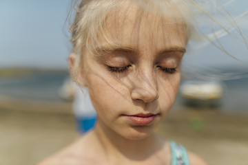 Close-up of girl with eyes closed standing at beach