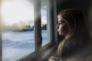 Side view of thoughtful girl standing by window at home