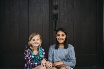 Portrait of friends sitting at doorway