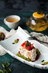 light dessert Anna Pavlova with raspberries and pistachios with a teapot and a cup of tea on a dark green concrete background