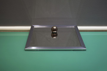 An abstract installation made of mirror and a metal sphere on top of a glass table