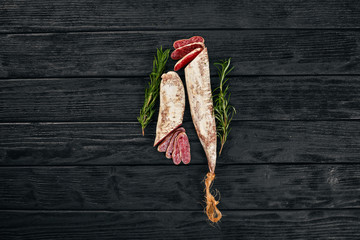 Fuet, Salami and Rosemary. Traditional Spanish sausage. On a black wooden background. Top view.