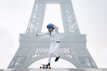 Full length of young woman skateboarding against Eiffel tower