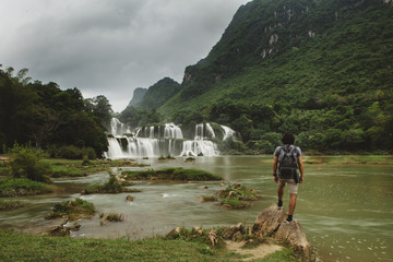 Rear view of man with backpack looking at waterfall while standing on rock against cloudy sky