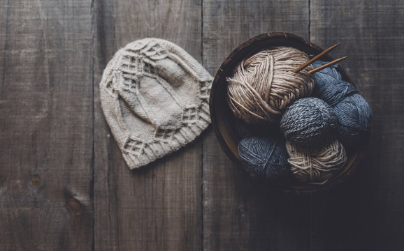 Overhead view of knit hat by woolen balls in bowl on table