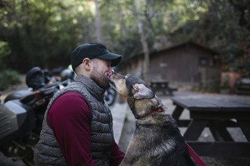 Dog licking man face while sitting in forest