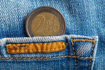 Euro coin with a denomination of two euro in the pocket of worn old blue denim jeans with orange seam