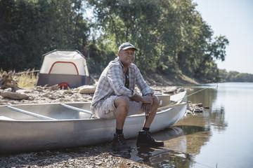 Man sitting on boat at lakeshore
