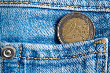 Euro coin with a denomination of 2 euro in the pocket of dark blue denim jeans
