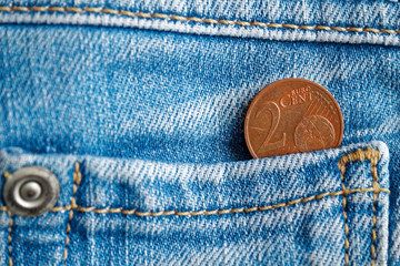 Euro coin with a denomination of 2 euro cent in the pocket of old worn blue denim jeans