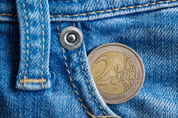 Euro coin with a denomination of two euro in the pocket of vintage old worn blue denim jeans